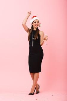 Volledig lengteportret van een vrolijke jonge vrouw die kleding draagt die kerstmis viert dat over roze achtergrond wordt geïsoleerd, die champagne drinkt uit een glas