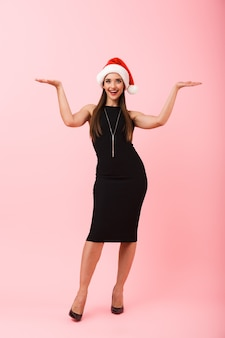 Volledig lengteportret van een vrolijke jonge vrouw die kleding draagt die kerstmis viert dat over roze achtergrond wordt geïsoleerd, die exemplaarruimte voorstelt