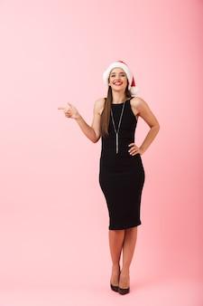 Volledig lengteportret van een vrolijke jonge vrouw die kleding draagt die kerstmis viert dat over roze achtergrond wordt geïsoleerd, wijzende vinger