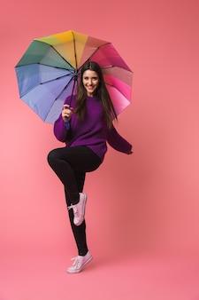 Volledig lengteportret van een vrolijke jonge vrouw die sweater draagt die met een paraplu loopt die over roze ruimte wordt geïsoleerd