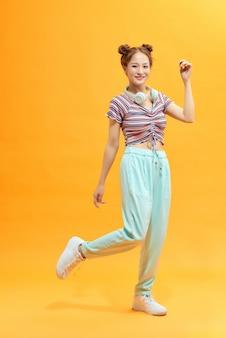 Volledig lengteportret van een vrolijke toevallige aziatische vrouw die geïsoleerd over gele achtergrond springt