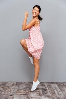 Volledig lengteportret van een vrolijke vrouw die haar succes viert dat op een grijze muur wordt geïsoleerd
