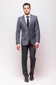 Volledig lengteportret van een zakenman die over grijze muur wordt geïsoleerd