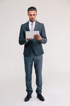 Volledig lengteportret van een zekere zakenman die geïsoleerde tabletcomputer met behulp van