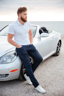 Volledig lengteportret van een zelfverzekerde bebaarde man die op zijn luxeauto leunt