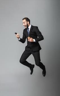 Volledig lengteportret van een zelfverzekerde knappe zakenman die geïsoleerd kostuum draagt, afhaalkoffie houdt, die mobiele telefoon gebruikt, het springen