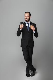 Volledig lengteportret van een zelfverzekerde knappe zakenman die geïsoleerd kostuum draagt, afhaalkoffie houdt, die mobiele telefoon gebruikt