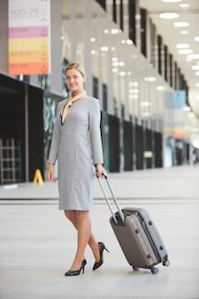 Volledig lengteportret van elegante blonde vrouw met koffer en glimlachen tijdens het wandelen in de luchthaven