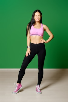 Volledig lengteportret van fitnessinstructeur in de sportschool op groene achtergrond