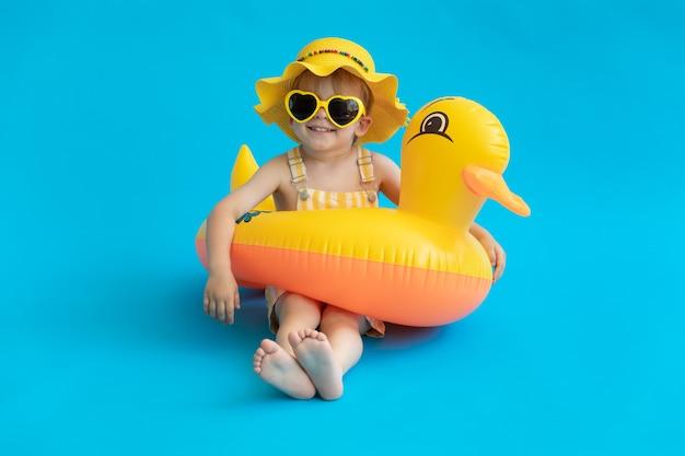 Volledig lengteportret van gelukkig kind met gele rubbereend tegen blauwe muur.