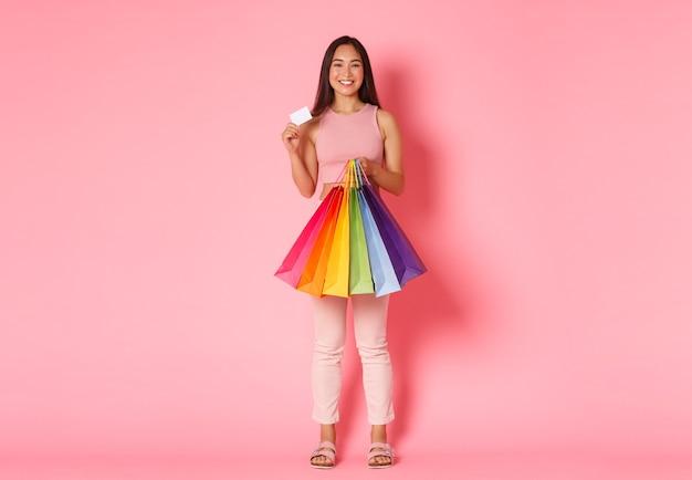 Volledig lengteportret van gelukkig trendy aziatisch meisje dat haar kortingscreditcard toont en boodschappentassen houdt, genietend van geld uitgeven aan nieuwe kleren, die zich over roze muur bevinden.