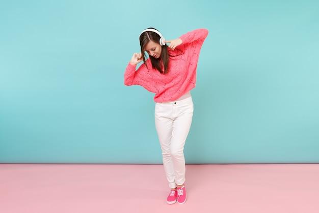 Volledig lengteportret van gelukkige jonge vrouw in gebreide roze trui, witte broek, koptelefoon