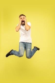 Volledig lengteportret van gelukkige springende die mens op geel wordt geïsoleerd