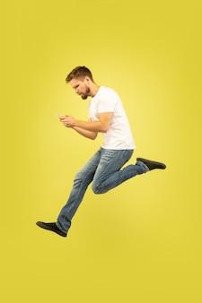 Volledig lengteportret van gelukkige springende mens die op gele achtergrond wordt geïsoleerd. kaukasisch mannelijk model in vrijetijdskleding. keuzevrijheid, inspiratie, concept van menselijke emoties. winnen bij sportweddenschappen.