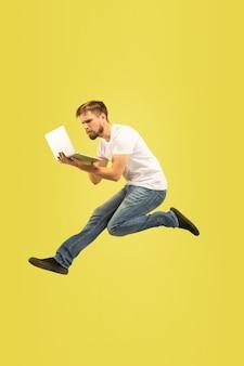 Volledig lengteportret van gelukkige springende mens die op gele achtergrond wordt geïsoleerd. kaukasisch mannelijk model in vrijetijdskleding