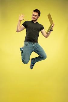 Volledig lengteportret van gelukkige springende mens met gadgets die op gele achtergrond worden geïsoleerd. moderne technologieën, concept van vrijheid van keuzes, concept van emoties. laptop gebruiken voor werk en plezier tijdens de vlucht.