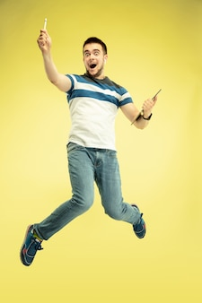 Volledig lengteportret van gelukkige springende mens met gadgets op geel.