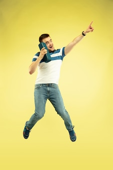 Volledig lengteportret van gelukkige springende mens met gadgets op geel