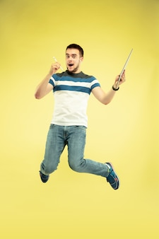 Volledig lengteportret van gelukkige springende mens met gadgets op gele achtergrond