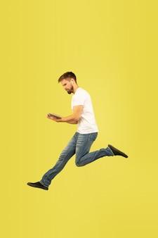 Volledig lengteportret van gelukkige springende mens op gele muur