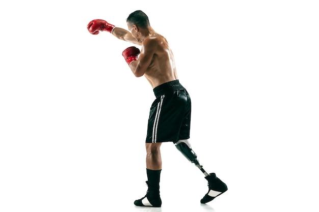 Volledig lengteportret van gespierde sportman met prothetisch been, kopieer ruimte. mannelijke bokser in rode handschoenen. geïsoleerd schot op witte muur.
