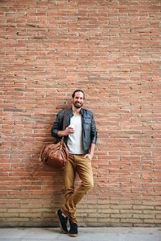 Volledig lengteportret van glimlachende europese man met vastgebonden haar die naar jou kijkt, terwijl hij over bakstenen muur op stadsstraat staat en afhaalkoffie drinkt