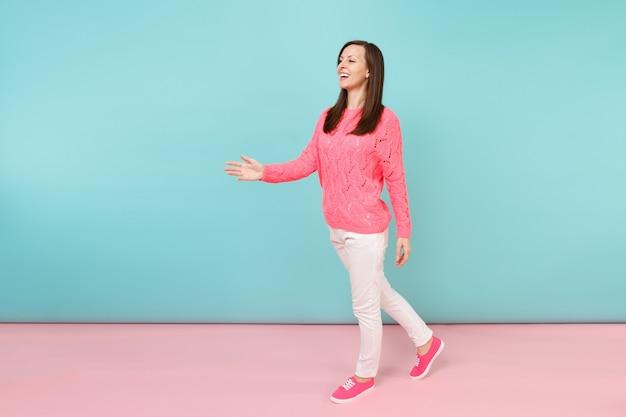 Volledig lengteportret van glimlachende jonge vrouw in gebreide roze trui, witte broek poseren
