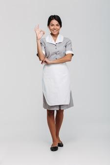 Volledig lengteportret van glimlachende mooie huishoudster in eenvormig tonend ok gebaar terwijl status