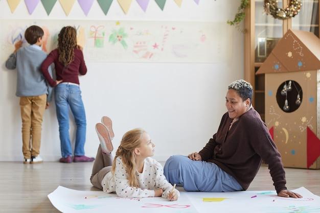 Volledig lengteportret van glimlachende vrouwelijke leraar zittend op de vloer met kinderen tekenen van afbeeldingen terwijl u geniet van kunstles op kerstmis, kopieer ruimte