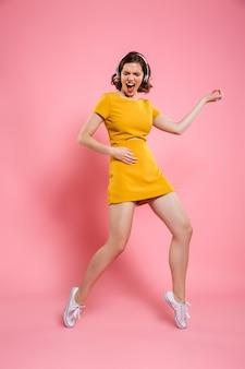 Volledig lengteportret van grappige mooie vrouw in gele kleding die pret heeft terwijl het spelen van luchtgitaar