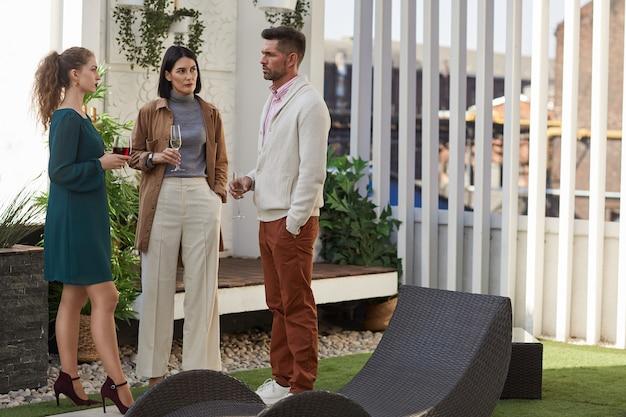 Volledig lengteportret van hedendaagse volwassen mensen die chatten terwijl ze tijdens het feest buiten op het terras staan,