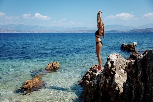 Volledig lengteportret van heet meisje in bikini die dichtbij overzees koelen