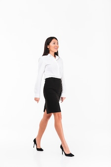 Volledig lengteportret van het gelukkige aziatische onderneemster lopen