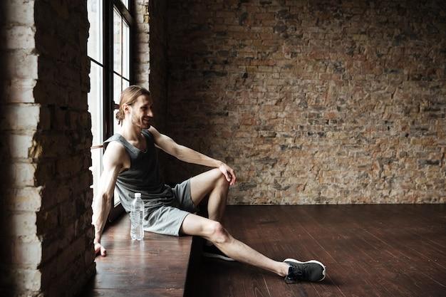 Volledig lengteportret van het glimlachen het gezonde sportman rusten