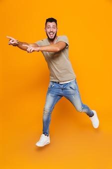 Volledig lengteportret van het glimlachen het toevallige jongeman springen