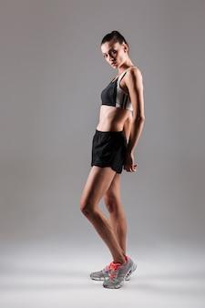 Volledig lengteportret van het slanke gezonde geschiktheidsvrouw stellen