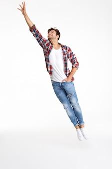 Volledig lengteportret van het toevallige aantrekkelijke mens springen