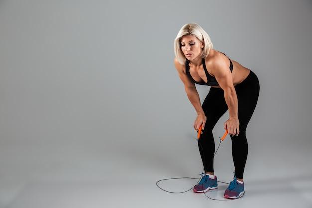 Volledig lengteportret van het vermoeide spier volwassen sportvrouw rusten