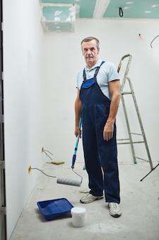 Volledig lengteportret van hogere bouwvakker die verfroller houdt en camera bekijkt tijdens het renoveren van huis, exemplaarruimte