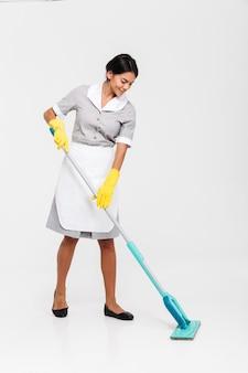 Volledig lengteportret van jonge aantrekkelijke vrouw in eenvormige schoonmakende vloer met zwabber