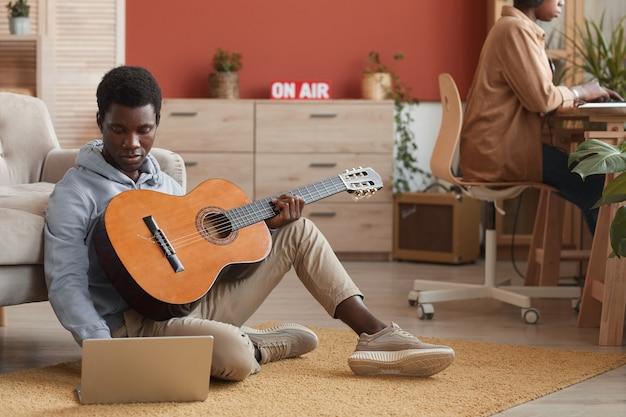 Volledig lengteportret van jonge afrikaans-amerikaanse muzikant die gitaar speelt en laptop gebruikt terwijl het zitten op vloer in opnamestudio, exemplaarruimte