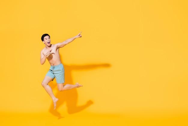 Volledig lengteportret van jonge gelukkige shirtless aziatische mens die in strandkledij in mid-air springen die twee vingers op lege ruimte naast in geel geïsoleerde muur richten