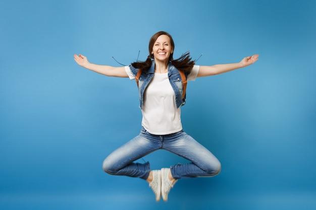 Volledig lengteportret van jonge glimlachende studente in denimkleren die het verspreiden van handen springen die voeten samenvoegen die op blauwe achtergrond wordt geïsoleerd. onderwijs aan de universiteit. kopieer ruimte voor advertentie.