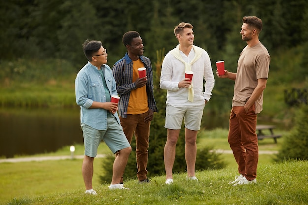Volledig lengteportret van jonge mannen die bier drinken en petten tijdens openluchtpartij in de zomer