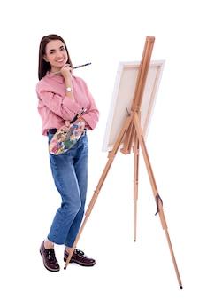 Volledig lengteportret van jonge mooie vrouwenkunstenaar met schildersezel, palet en verfborstel die op witte achtergrond wordt geïsoleerd