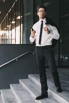 Volledig lengteportret van jonge ondernemer gekleed in formeel kostuum dat zich buiten het glazen gebouw met jasje over zijn schouder bevindt, en mobiele telefoon houdt