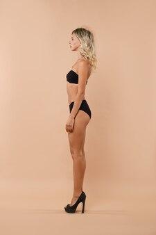 Volledig lengteportret van jonge vrouw in zwarte lingerie en hoge hakken die zich in profiel bevinden