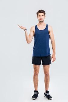 Volledig lengteportret van knappe zelfverzekerde aantrekkelijke jonge sportman die copyspace op de palm houdt over grijze achtergrond