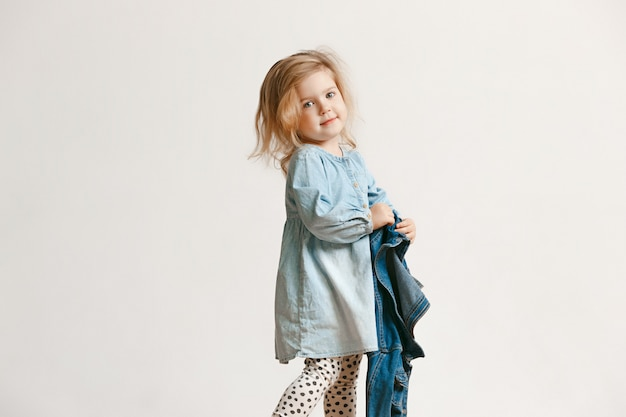 Volledig lengteportret van leuk klein jong geitjemeisje in modieuze jeanskleren en glimlachen, die zich op wit bevinden. kindermode concept
