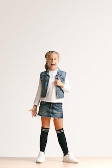 Volledig lengteportret van leuk klein tienermeisje in modieuze jeanskleren die camera bekijken en tegen witte studiomuur glimlachen. kindermode concept